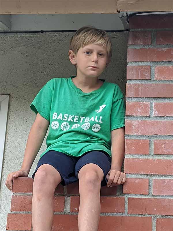 Young boy sitting on a brick wall looking at camera