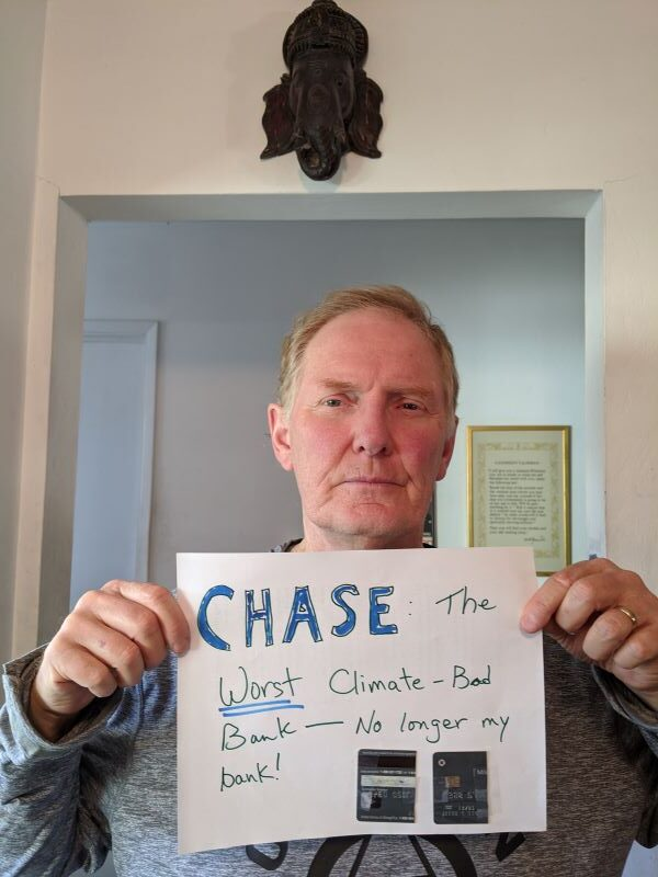 a man holding up a sign that says Chase the worst climate-bad bank. No longer my bank