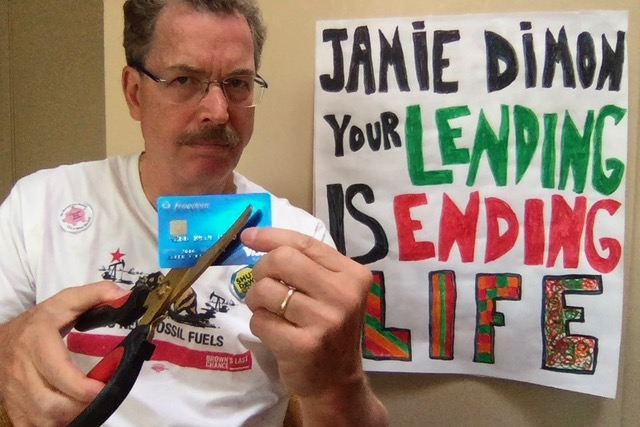 Man with scissors cutting up his credit card next to sign that says Jamie Dimon your lending is ending life