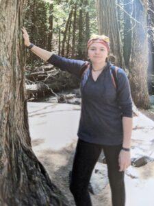 Girl leans against tree