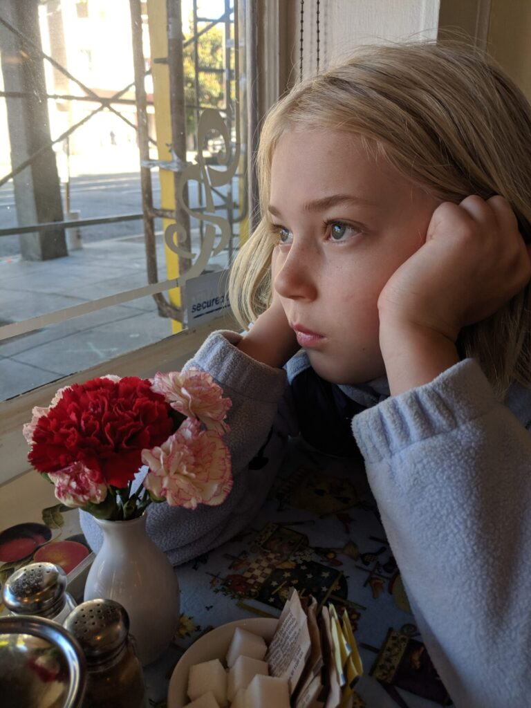 Girl with flowers looks out a window