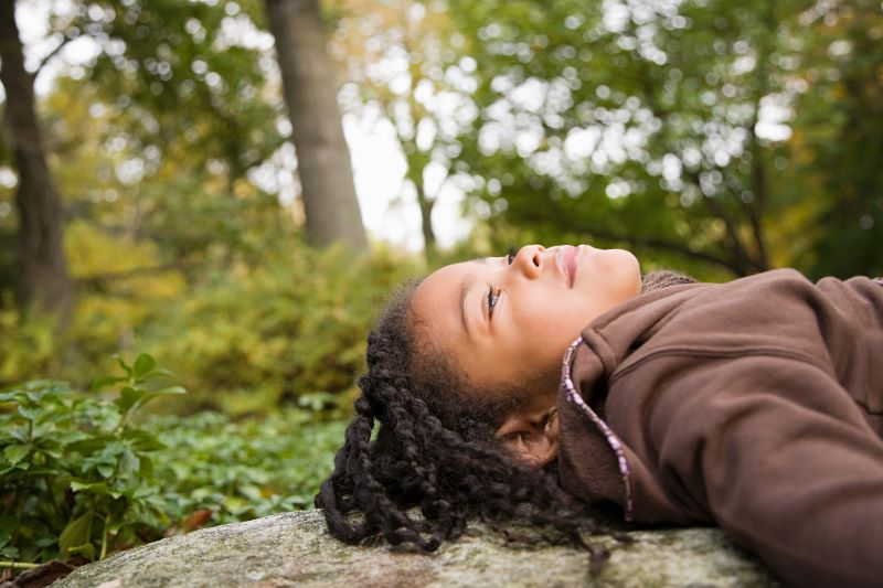 girl laying on a rock looking up