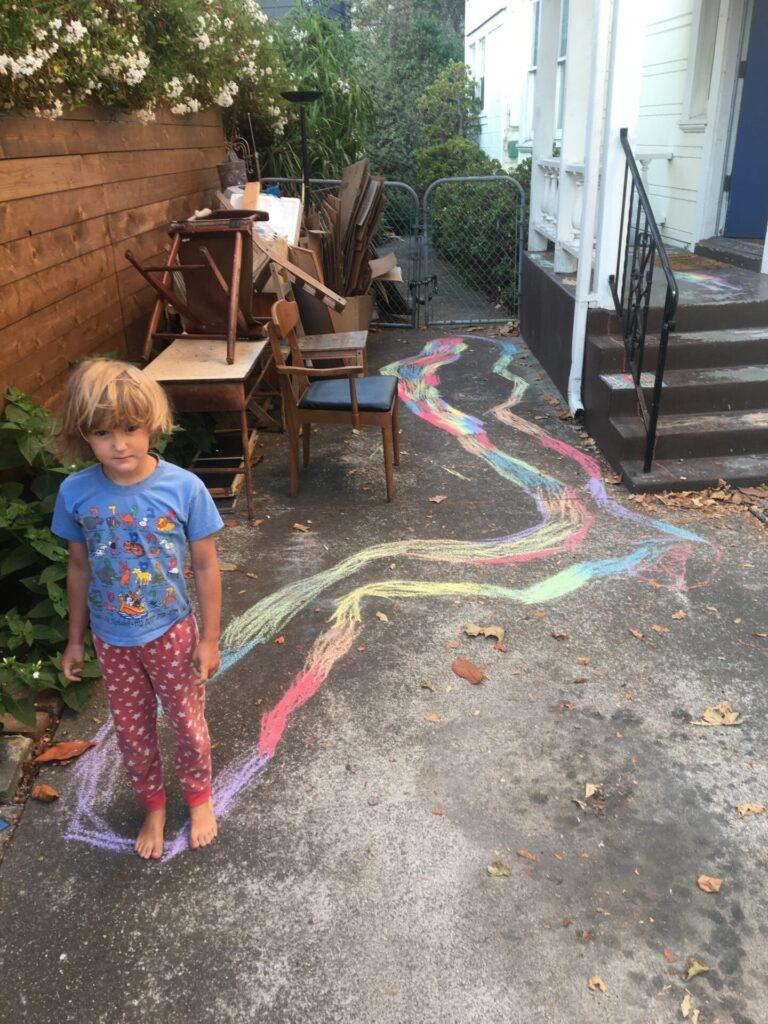 Girl draws with rainbow chalk